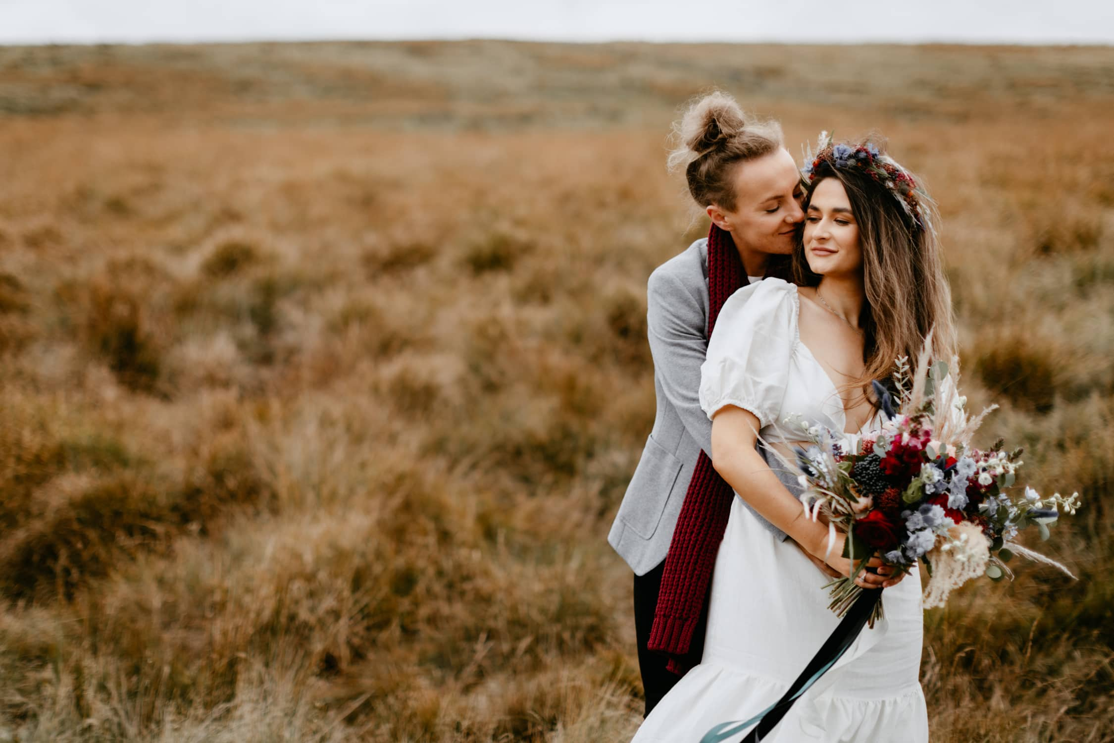 Two brides embrace on moorland