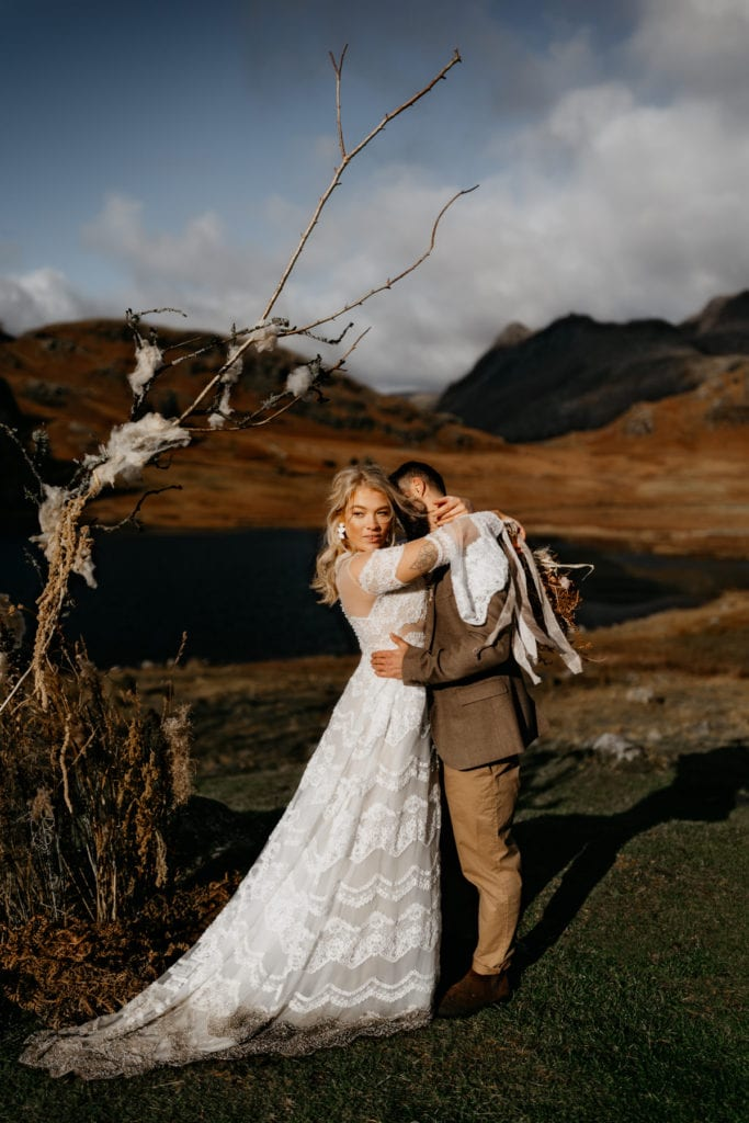 Bride and groom embrace by lake and mountains