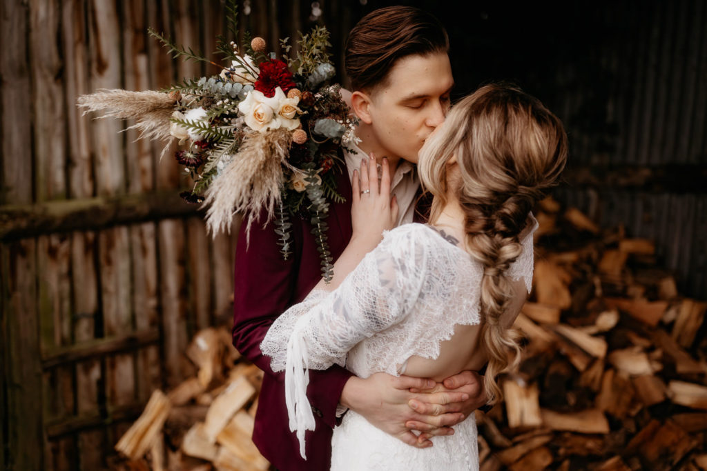 Scotland woodland elopement couple in a wood shed kissing