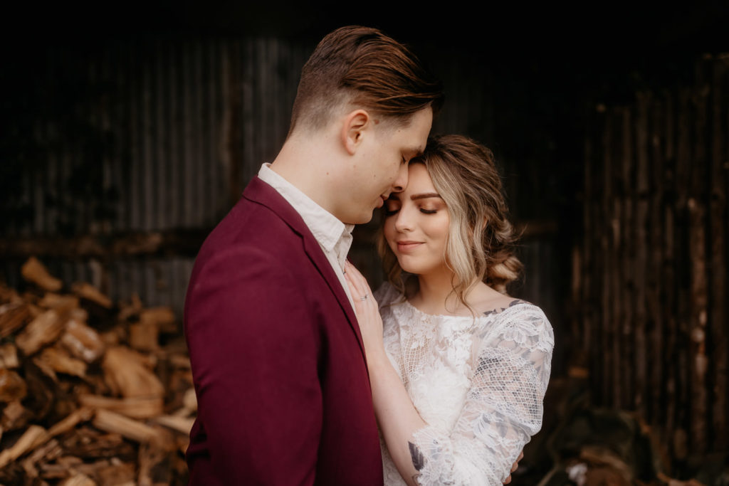 Scotland woodland elopement couple in a wood shed forehead kiss