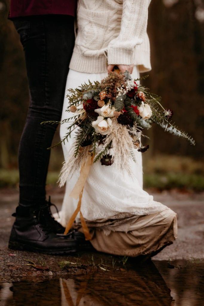 Elopement bouquet flowers and muddy wedding dress