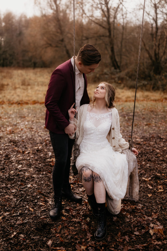 Scotland woodland elopement couple gazing into each other's eyes. She is sitting on a swing, he is looking down at her.