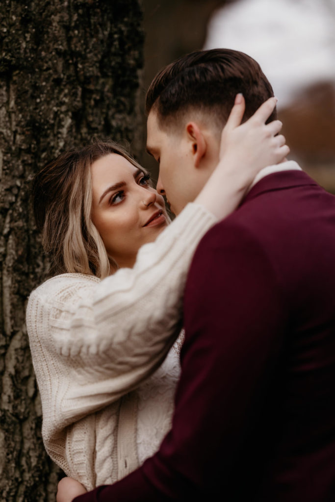 Elopement couple embracing by a tree in a woodland