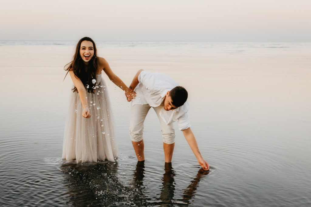 Eloping couple splashing in the sea, Outer Hebrides
