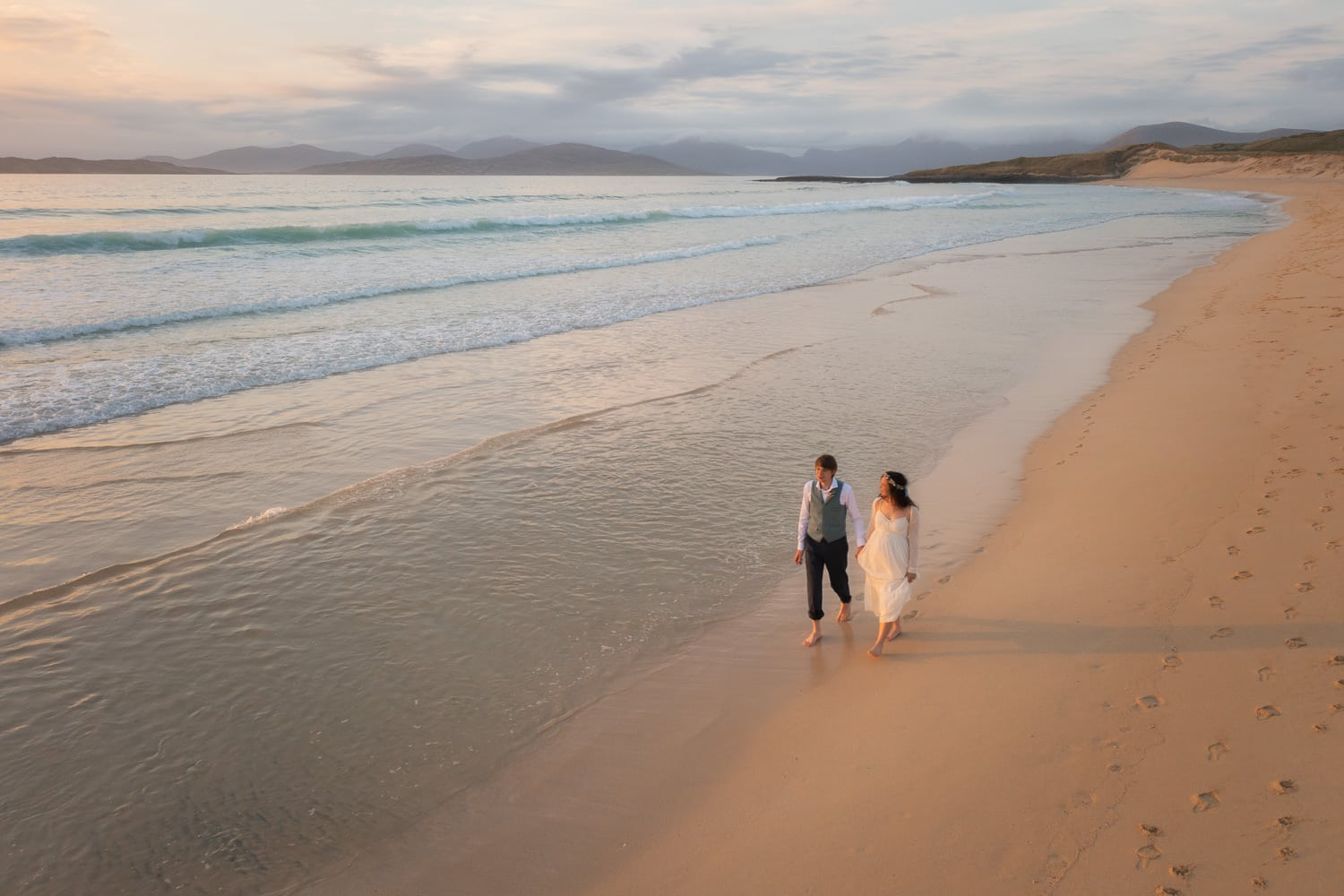 Eloping couple walking along Scarista beach at sunset, Isle of Harris, Outer Hebrides